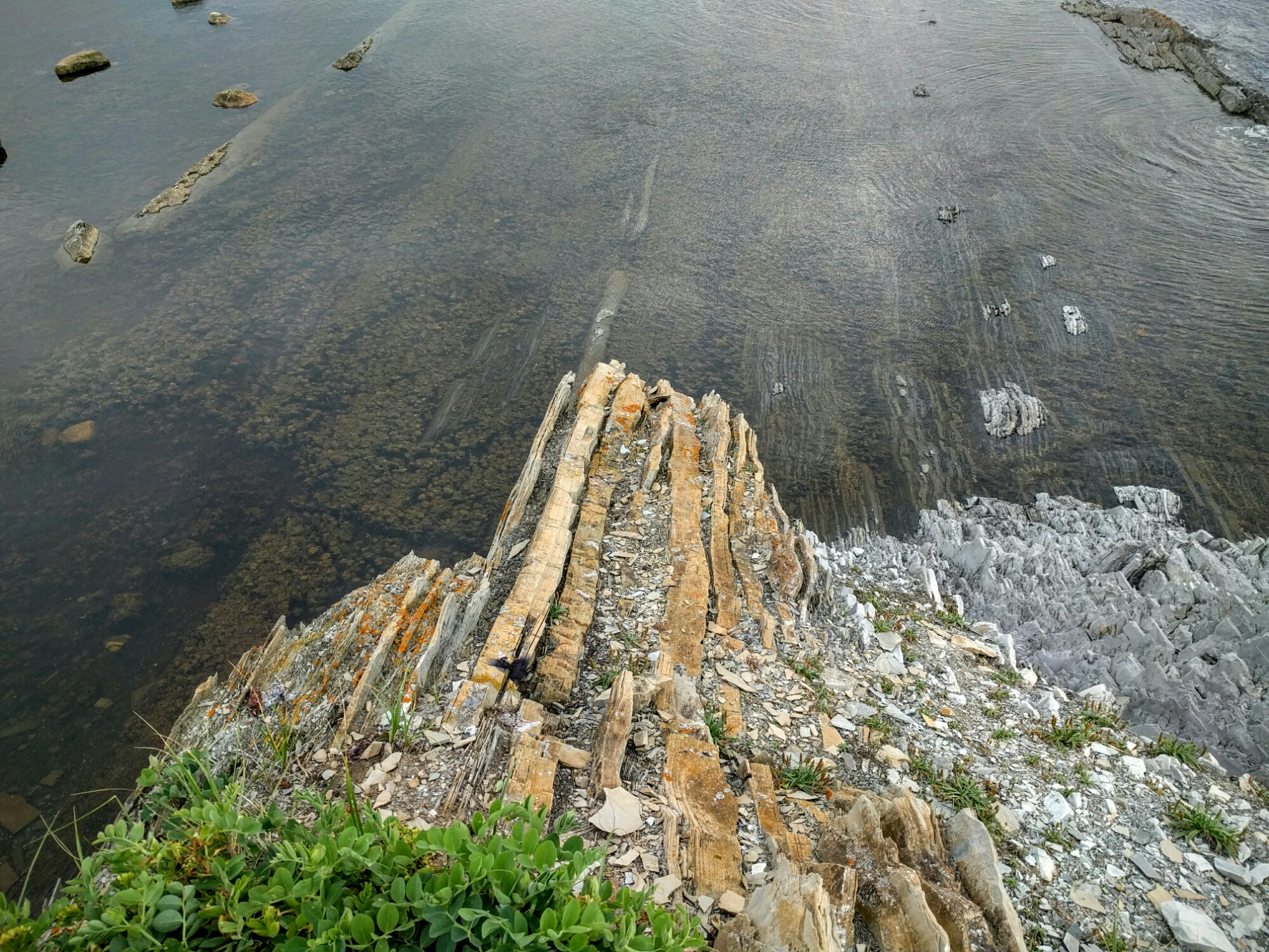 The tide rolls in and covers the exposed rock cliffs.